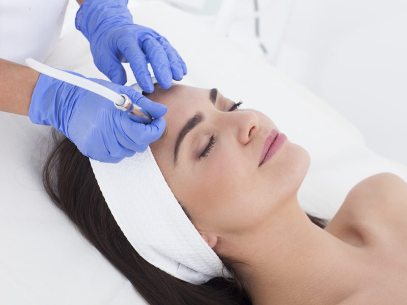 Microdermabrasion being performed on a woman laying down at a laser center